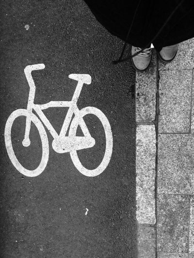 Cropped image of man standing by bicycle drawing on road