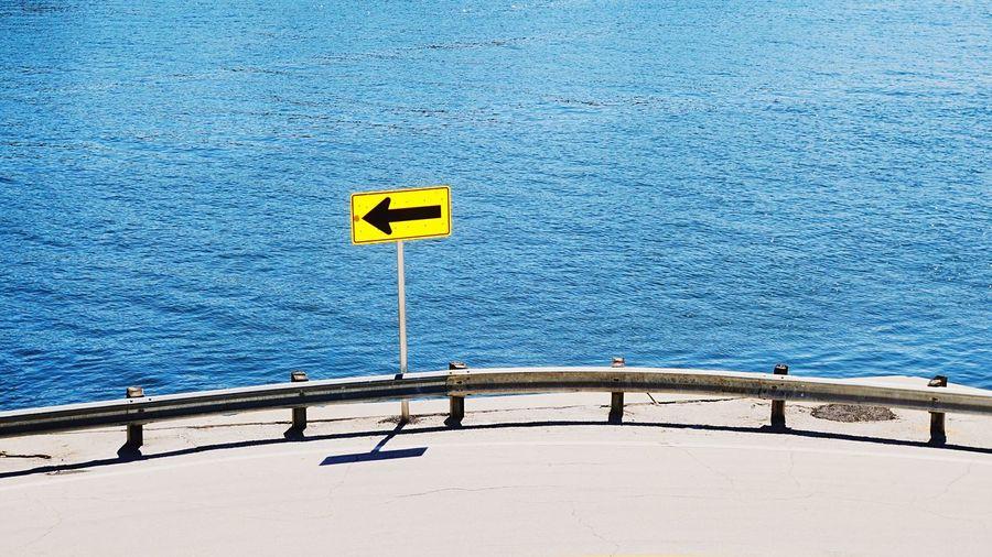 Arrow sign by sea against sky