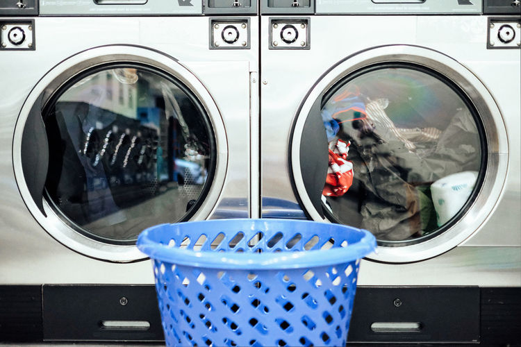 Close-up of basket against the washing machine in launderette