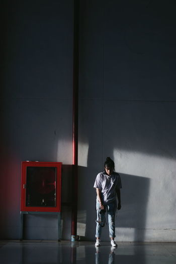 Full length of young woman standing by wall in building