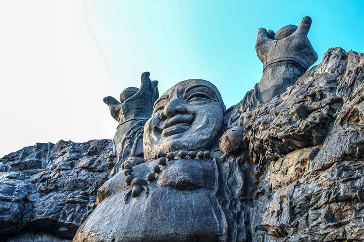 Low angle view of statue against rock formation