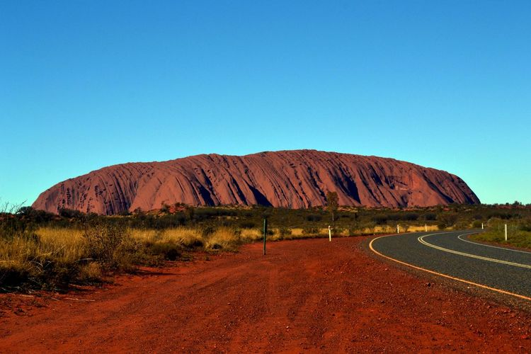 SCENIC VIEW OF EMPTY ROAD LEADING TOWARDS ROCK FORMATION