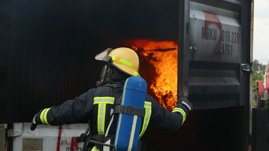 Rear View Of Firefighter By Burning Building