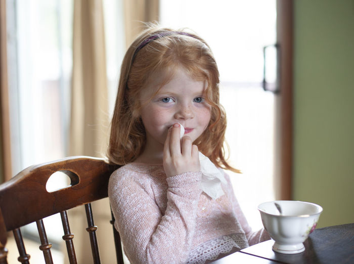 A five-year-old girl with red hair and blue eyes wipes her mouth after drinking tea during a tea party at her home. Childhood One Person Indoors  Portrait Sitting Real People Females Innocence Child Drink Home Interior Food And Drink Cute Lifestyles Casual Clothing Headshot Girls Looking Away Hairstyle Tea Party Tea Napkin Decorum Red Hair Blue Eyes