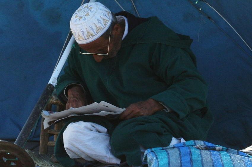2011 Day Glasses Jamaa El Fna Man Marrakesh Morocco Newspaper Reading Real People Sitting Sun Umbrella White Cap