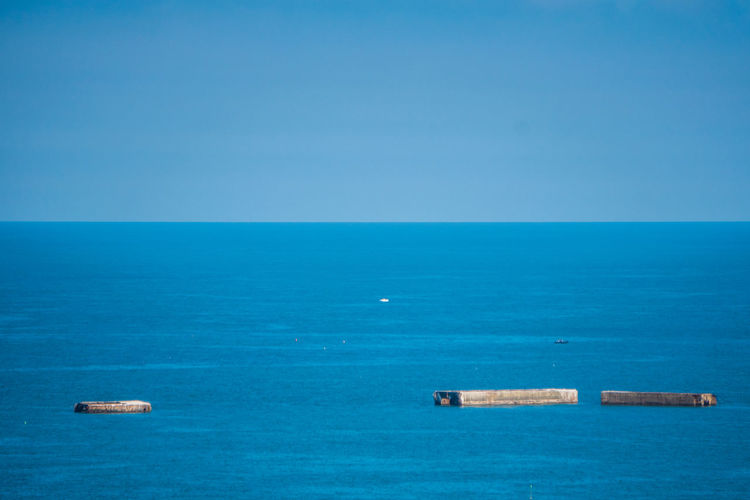 Scenic view of blue sea and mulberry against clear sky