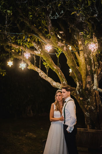 Couple standing by illuminated tree at night