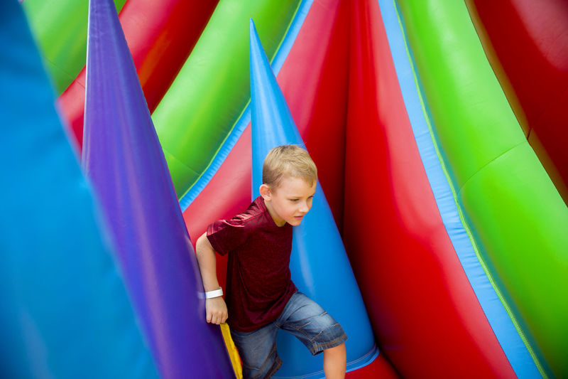 Boy Playing On Colorful Bouncy Castle