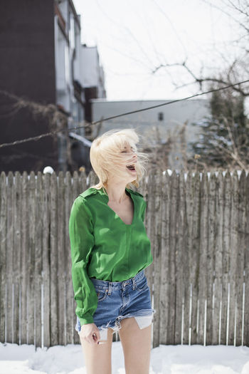 Midsection of woman standing by fence
