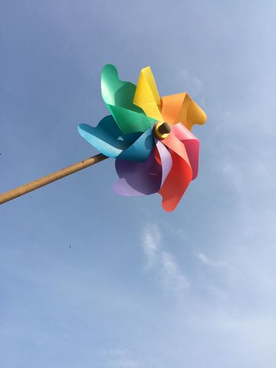 Low angle view of colorful pinwheel toy against sky