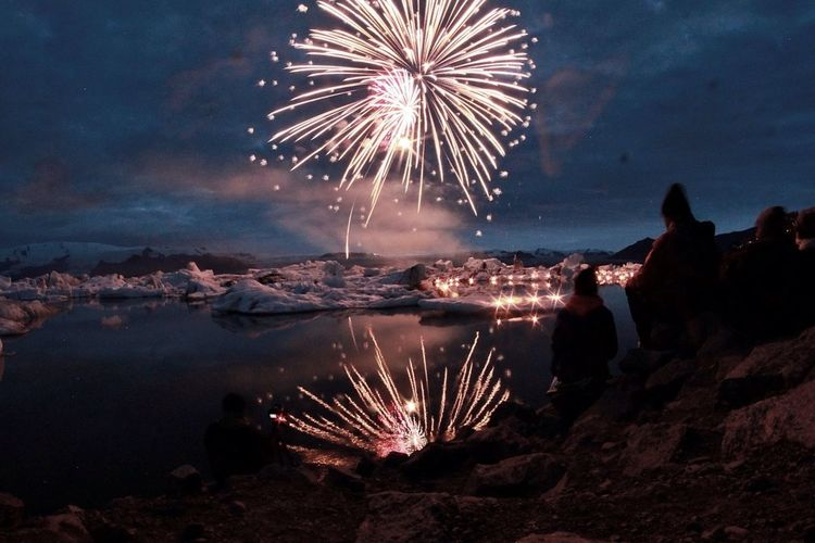 People by lake looking at firework display during dusk