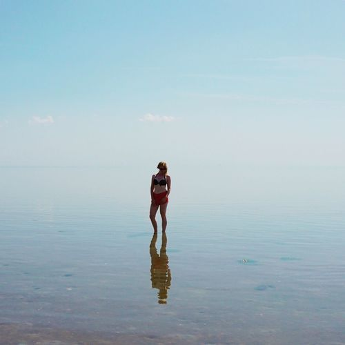 Young woman standing amidst sea against sky