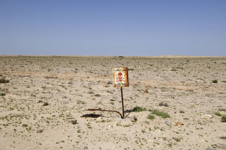 Mines along the road through the Western Sahara on the road to Mauritania Danger Sign Desert Sahara Desert Sign Danger Danger Mines Dangerous Dangerzone Mines Rusty Rusty Sign Sahara Sand Sighn Signboard Skull Skull Face Western Sahara