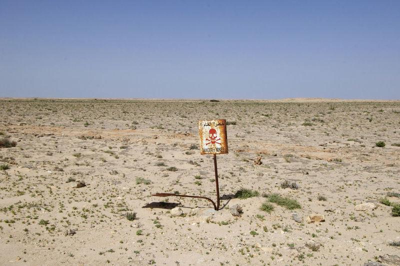 Warning Sign In Desert Against Clear Sky