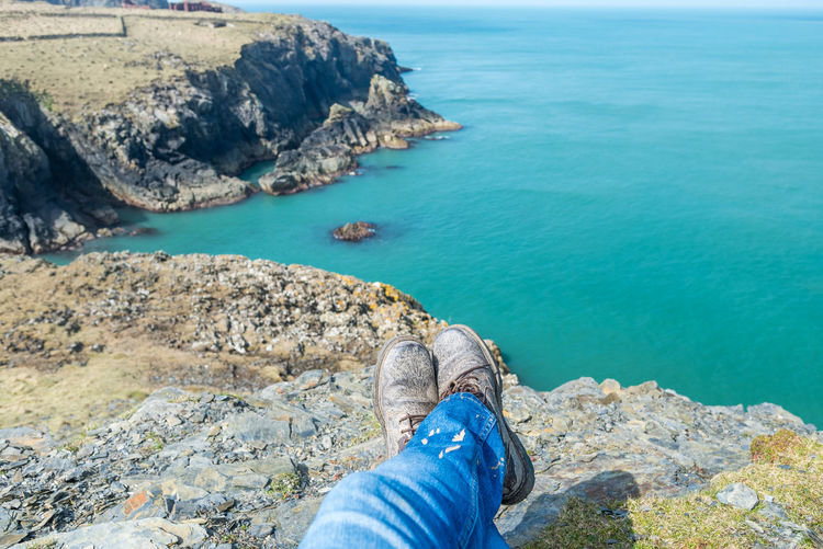 Low section of person on rock against sea