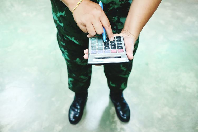 Low section of army soldier using calculator