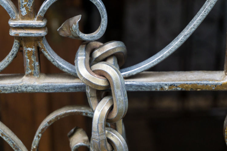 Close-up of chain on metal gate