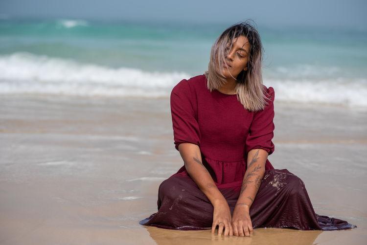 Full length of woman sitting on beach