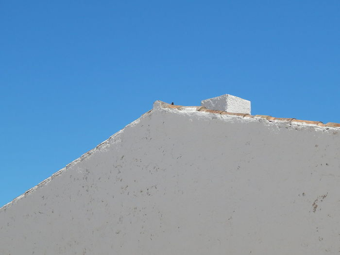 roof and blue sky Roof Rooftop Azure Blue Blue Sky Blue Sky And Clouds Building Building Exterior Built Structure Clear Sky Low Angle View Monochrome Monochrome _ Collection No People Outdoors Roof Roofs Rooftop View  Rooftops Sky Stone Wall Sunlight Wall Wall - Building Feature White Color