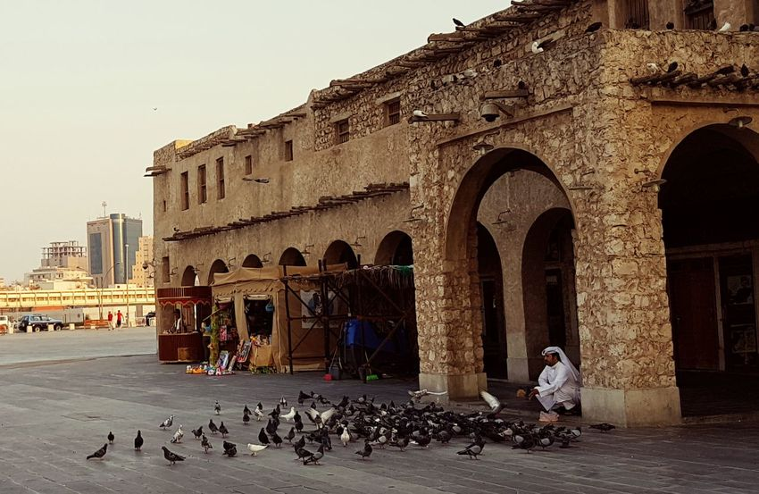 Feeding the pigeons Feeding The Birds Architecture Built Structure City Souq Waqif Adapted To The City Feeding The Birds Travel Samsungphotography Streetphotography Pigeons Old Town Building Stories From The City