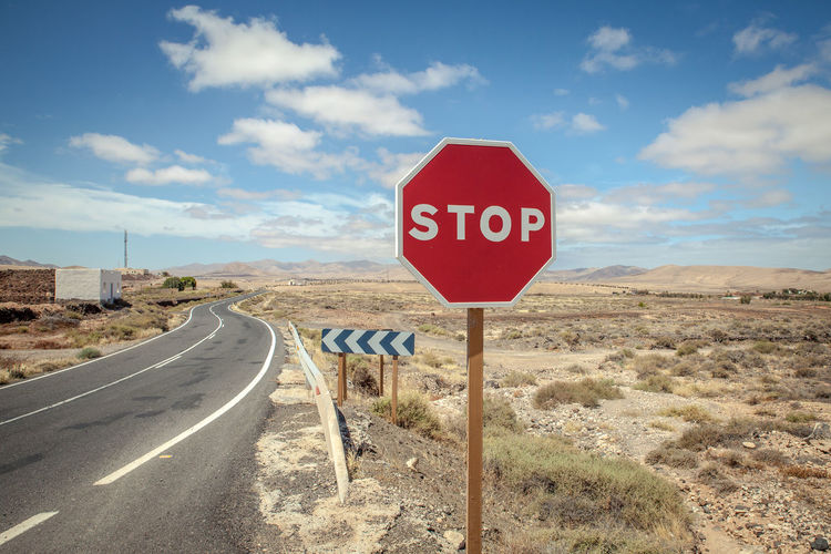 Blue Day Desert Fuerteventura Landscape Mediterranean  No People Outdoors Red Road Road Sign Sky Stop Stop Sign Text Transportation Winding Road