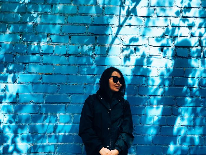 Woman wearing sunglasses standing against blue wall