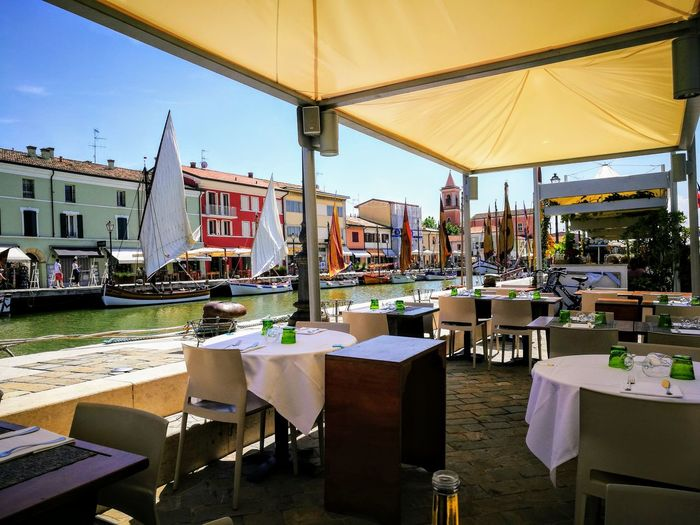 Boats⛵️ Canal Cesenatico Porto Canale City Awning Table Chair Sky Architecture Food And Drink Restaurant Menu Outdoor Cafe