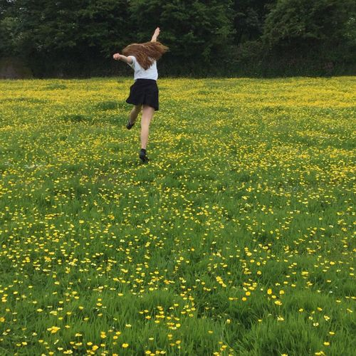 Rear view of girl jumping on yellow flowerbed on field