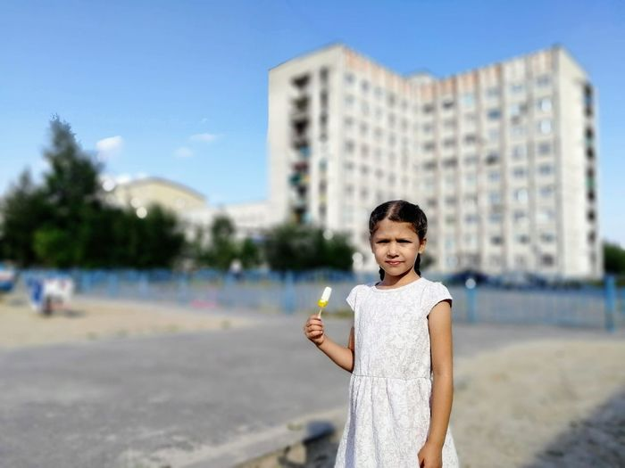 Portrait of cute girl holding flavored ice while standing in city
