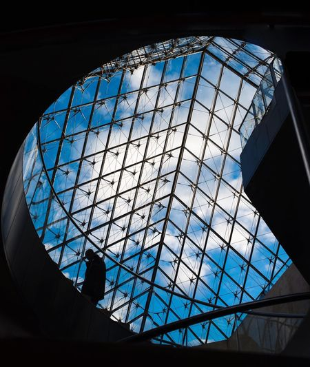 A security guard walking up the stairs Pyramid Halfwayup Paris Staircase To Heaven Walkup Architecture Blue Blue Sky Building Exterior Built Structure City Glass - Material Indoors  Louvremuseum Low Angle View Modern Sky