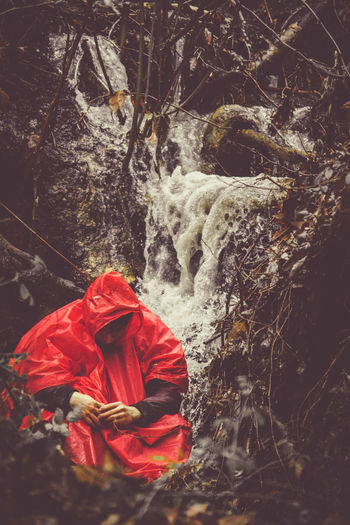 Man Wearing Red Raincoat While Sitting Against Waterfall Forest