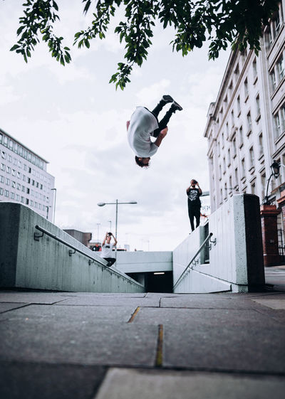 Architecture Building Exterior Built Structure City Day Flying Full Length Leisure Activity Lifestyles Men Mid-air Motion Nature One Person Outdoors Real People Skill  Sky Stunt