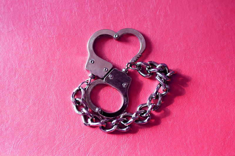 Directly Above Shot Of Metal Handcuffs On Pink Table