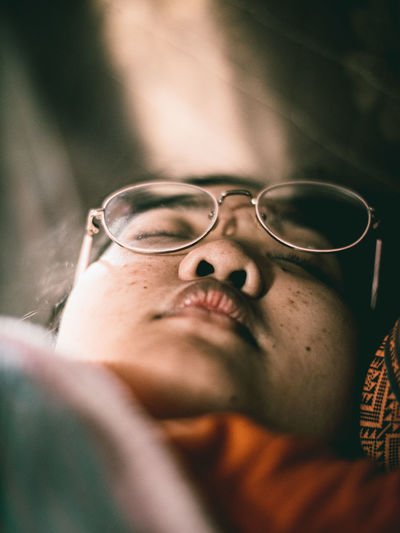 Close-up of woman wearing eyeglasses lying down at home