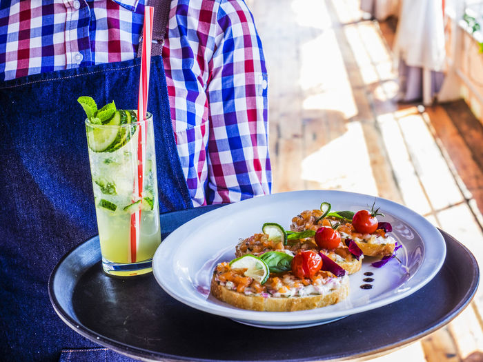 Midsection of waitress carrying tray with open faced sandwiches and lemonade at restaurant