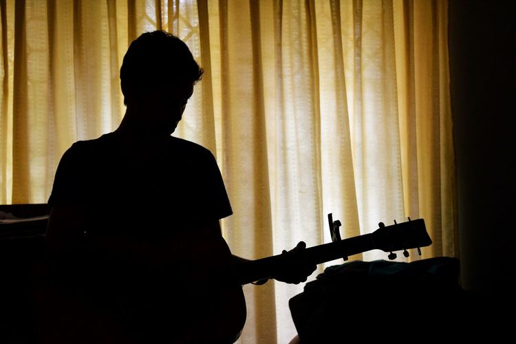 Rear view of silhouette young man playing guitar at home