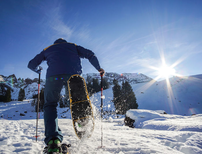 Beauty In Nature Cold Temperature Day Leisure Activity Lens Flare Lifestyles Mountain Nature One Person Outdoors Real People Rear View Skiing Sky Snow Sport Sun Sunbeam Sunlight Warm Clothing Winter Winter Sport EyeEmNewHere