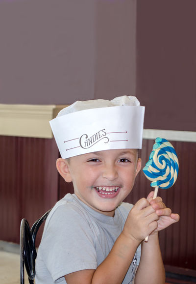 A happy little boy laughs as he eats a giant sweet lolly pop person Happy Hat Kids Sugar Boys Child Childhood Emotion Front View Happiness Headshot Hispanic Holding Indoors  Innocence Lifestyles Lollypop Looking At Camera Males  One Person Portrait Real People Smiling Sweet Food