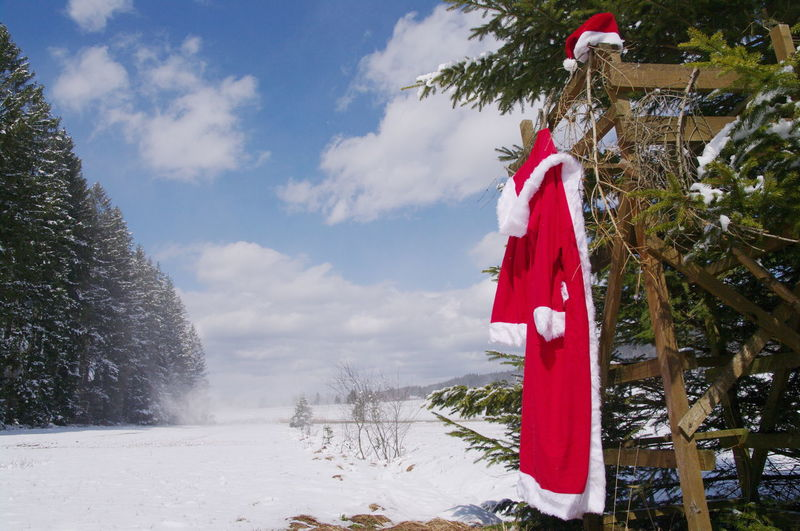 Santa Claus Costume Hanging On Tree During Winter