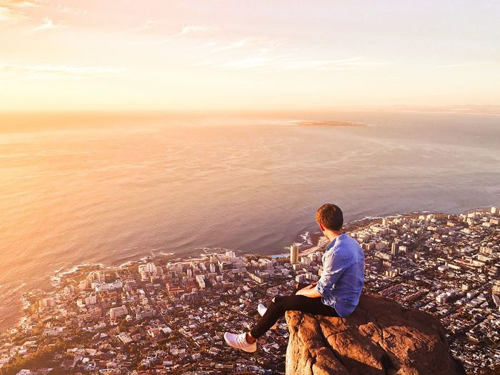 sunset above the city 🌅 Wanderland Wanderlust ReiseReise Dressed Up Vitaminsea Oceanview Mothercity Westerncape Lionsheadpeak Lionshead LookAtThoseColours Southafrica Capetown Water Sea Beauty In Nature Leisure Activity Lifestyles Sitting Sky Real People Nature One Person Land Men Sunlight Scenics - Nature Sunset Idyllic Horizon Over Water
