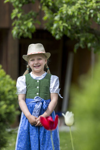 Portrait of cute smiling girl standing at public park