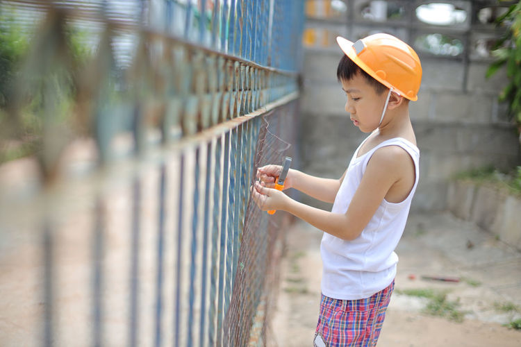 Side view of boy cutting fence