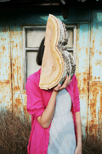 Casual Clothing Unrecognizable Person Obscured Face Women Holding Outdoors Leisure Activity Hiding Front View Wood Log Girl Young Adult Young Women Colorful Building Exterior Weird Strange Odd Anonymous Noface Surreal Window Rust Corrosion