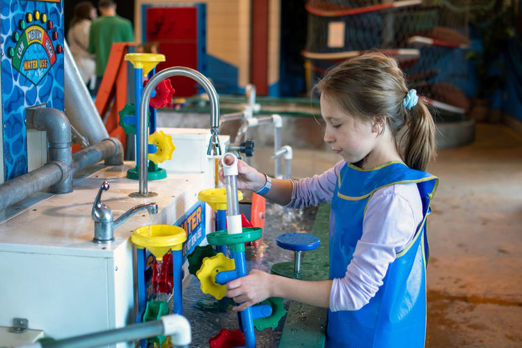 An indoor water table teaches a girl about connection, direction, engineering and structure.