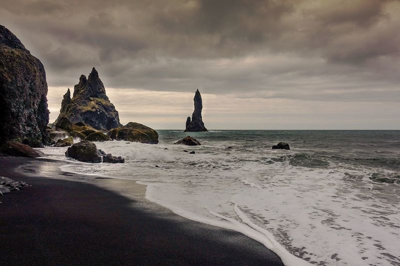 Reynisfjara Iceland Sea Beach Water Scenics Shore Cloud - Sky Sky Wave Remote Rock Formation Outdoors Cloudy Non-urban Scene Vacations Dramatic Sky Nature Travel Destinations Power In Nature