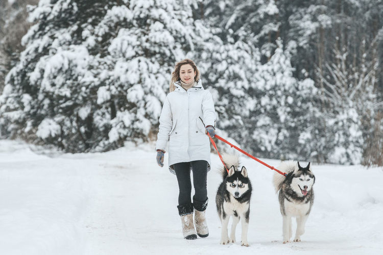 Portrait of woman with dog standing in snow