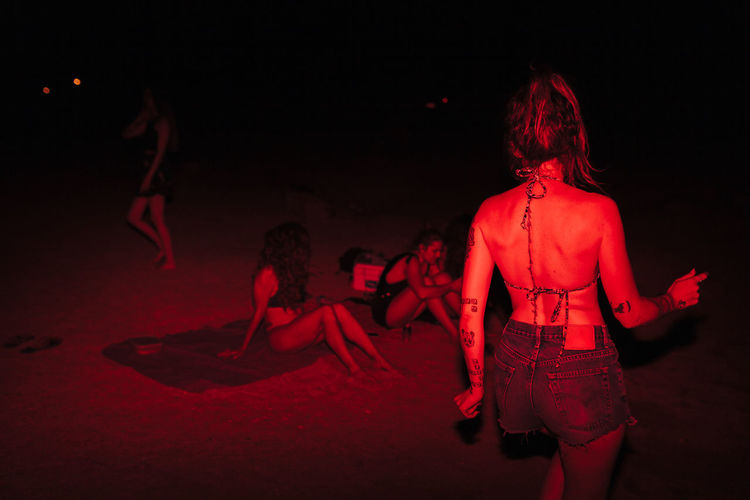 Rear view of woman dancing at night outdoors