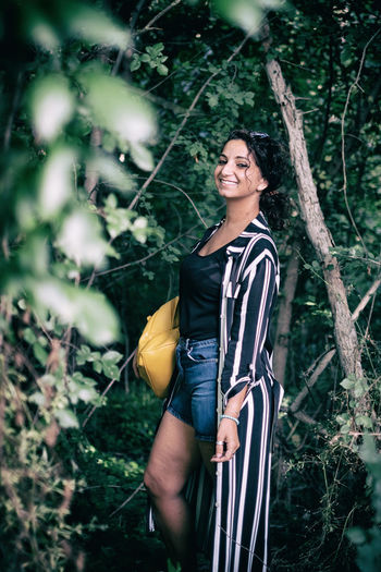Portrait of smiling young woman standing on tree