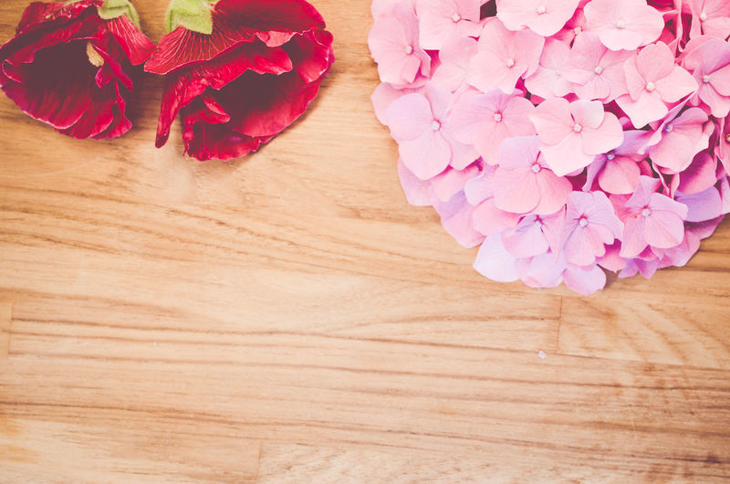 Directly above shot of pink hydrangea and red roses on table