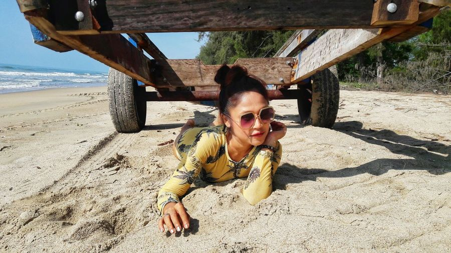 Young Woman Lying On Sand Below Wooden Trailer